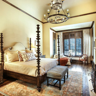 This is an example of a large mediterranean master bedroom in Dallas with yellow walls, medium hardwood floors, a standard fireplace, a stone fireplace surround and brown floor.