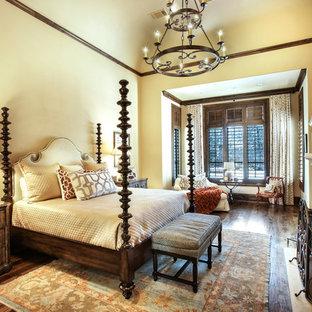 Foto di una grande camera matrimoniale mediterranea con pareti gialle, pavimento in legno massello medio, camino classico, cornice del camino in pietra e pavimento marrone