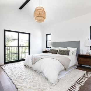 ロサンゼルスの中くらいの地中海スタイルのおしゃれな主寝室 (白い壁、無垢フローリング、コーナー設置型暖炉、茶色い床、三角天井) のインテリア