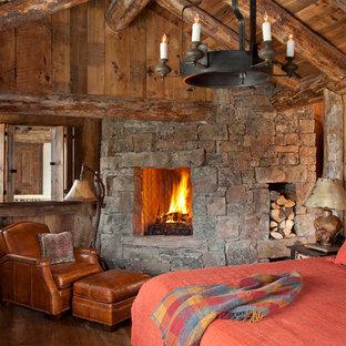 Idee per una camera da letto rustica con parquet scuro, cornice del camino in pietra e camino ad angolo