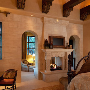 Photo of an expansive traditional master bedroom in Phoenix with brown walls, terra-cotta floors, a two-sided fireplace and a stone fireplace surround.