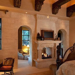 Esempio di un'ampia camera matrimoniale tradizionale con pareti marroni, pavimento in terracotta, camino bifacciale e cornice del camino in pietra