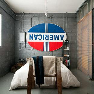 Inspiration för ett industriellt sovrum, med grå väggar och betonggolv