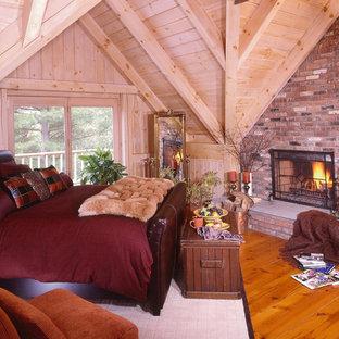 Imagen de dormitorio principal con suelo de madera en tonos medios, chimenea tradicional y marco de chimenea de piedra