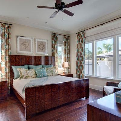 Example of an island style dark wood floor bedroom design in Tampa with beige walls
