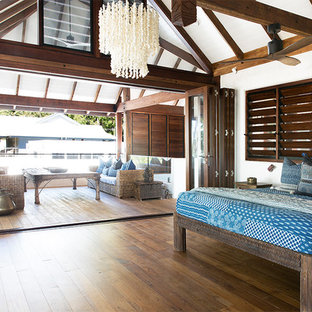 Design ideas for a tropical bedroom in Cairns with white walls, dark hardwood floors and brown floor.