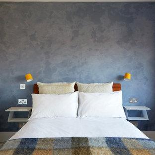 Imagen de dormitorio principal, actual, pequeño, sin chimenea, con paredes azules, suelo de madera clara y suelo beige
