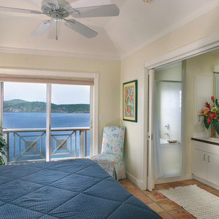 This is an example of a beach style bedroom in Other with beige walls and terra-cotta floors.