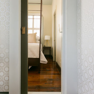 Diseño de dormitorio principal, retro, grande, con suelo de madera en tonos medios, chimenea de esquina y marco de chimenea de madera