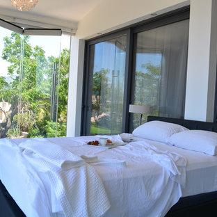 Imagen de dormitorio principal, grande, sin chimenea, con paredes blancas y suelo de travertino