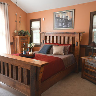 This is an example of an arts and crafts bedroom in Charlotte with orange walls and carpet.