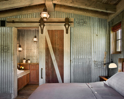 Example of a country bedroom design with gray walls and dark hardwood ...