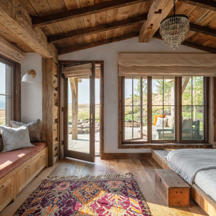 Inspiration for a rustic master bedroom in Other with white walls, medium hardwood flooring and no fireplace.