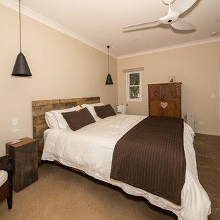 Ejemplo de dormitorio principal, de estilo de casa de campo, de tamaño medio, con paredes beige, suelo de cemento, marco de chimenea de piedra y estufa de leña