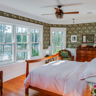 This is an example of a mid-sized traditional master bedroom in Portland Maine with green walls, dark hardwood floors, no fireplace and orange floor.