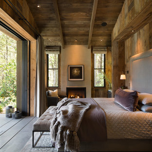 Bedroom - farmhouse master concrete floor bedroom idea in San Francisco with brown walls, a standard fireplace and a plaster fireplace