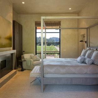 Imagen de dormitorio principal, de estilo de casa de campo, de tamaño medio, con paredes beige, suelo de piedra caliza, chimenea tradicional y marco de chimenea de metal