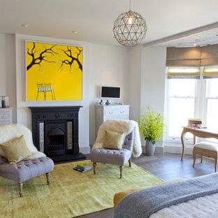 Imagen de dormitorio principal, costero, con paredes blancas, suelo de madera en tonos medios y chimenea tradicional