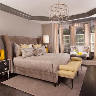 Imagen de dormitorio principal, clásico renovado, grande, con suelo de madera oscura, paredes grises, chimenea tradicional, marco de chimenea de madera y suelo marrón