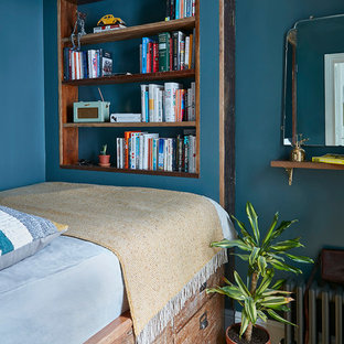 Design ideas for a small traditional guest bedroom in London with blue walls, medium hardwood flooring and brown floors.