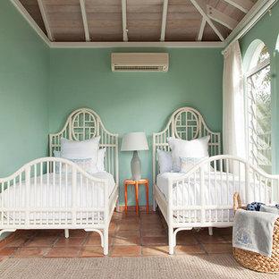 Esempio di una piccola camera degli ospiti tropicale con pareti verdi, pavimento in terracotta, nessun camino e pavimento arancione