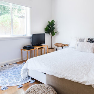 Beach style guest bedroom in Melbourne with white walls, medium hardwood floors and brown floor.