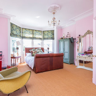 This is an example of a bohemian bedroom in Sussex with pink walls and carpet.