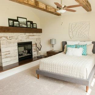 Ejemplo de dormitorio principal, tradicional renovado, extra grande, con paredes blancas, moqueta, chimenea de doble cara, marco de chimenea de madera y suelo beige