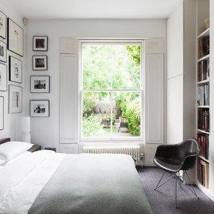 Foto på ett funkis gästrum, med vita väggar, heltäckningsmatta och en standard öppen spis