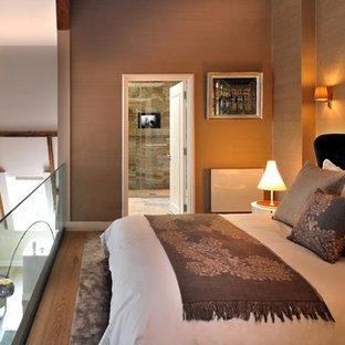 Inspiration pour une chambre mansardée ou avec mezzanine design de taille moyenne avec un mur beige et un sol en bois brun.