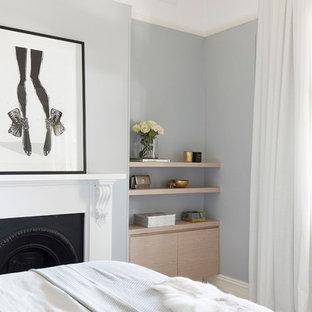 На фото: хозяйская спальня среднего размера в современном стиле с синими стенами, ковровым покрытием, стандартным камином, фасадом камина из штукатурки и бежевым полом с