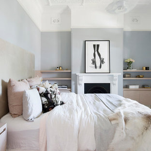 Design ideas for a mid-sized scandinavian master bedroom in Sydney with blue walls, carpet, a standard fireplace, a plaster fireplace surround and beige floor.