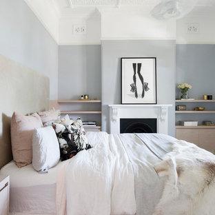 Diseño de dormitorio principal, nórdico, de tamaño medio, con paredes azules, moqueta, chimenea tradicional, marco de chimenea de yeso y suelo beige