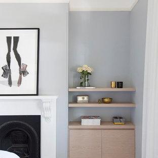 На фото: с высоким бюджетом хозяйские спальни среднего размера в современном стиле с синими стенами, ковровым покрытием, стандартным камином, фасадом камина из штукатурки и бежевым полом