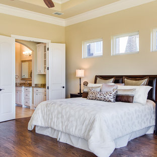 This is an example of an expansive traditional master bedroom in Dallas with yellow walls, dark hardwood floors, no fireplace and brown floor.