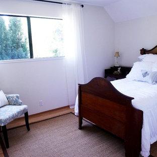 Foto de habitación de invitados tradicional, de tamaño medio, sin chimenea, con paredes amarillas y suelo de madera oscura