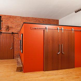 Exemple d'une chambre mansardée ou avec mezzanine industrielle de taille moyenne avec un sol en bois clair et un mur orange.