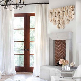 Inspiration for a mediterranean bedroom in Austin with white walls, medium hardwood floors and a corner fireplace.