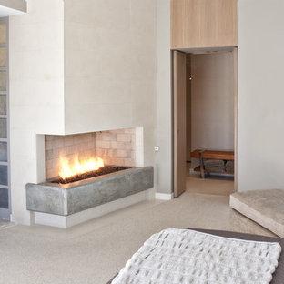 Modelo de dormitorio actual con marco de chimenea de hormigón y chimenea de esquina