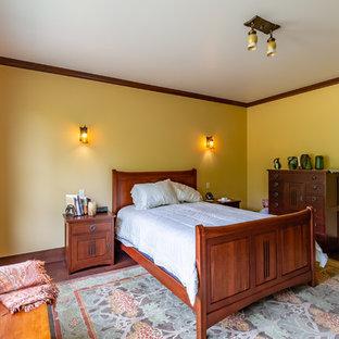 シアトルのヴィクトリアン調のおしゃれな主寝室 (濃色無垢フローリング、標準型暖炉、木材の暖炉まわり、茶色い床) のインテリア