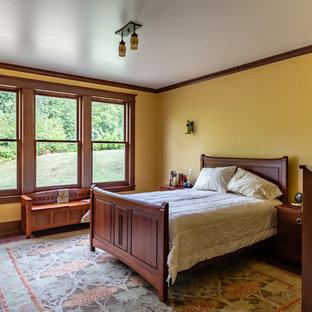 シアトルのヴィクトリアン調のおしゃれな主寝室 (茶色い床、黄色い壁、無垢フローリング)