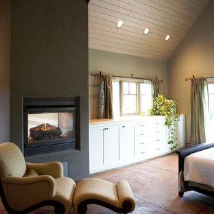 Imagen de dormitorio ecléctico con marco de chimenea de hormigón y chimenea de doble cara