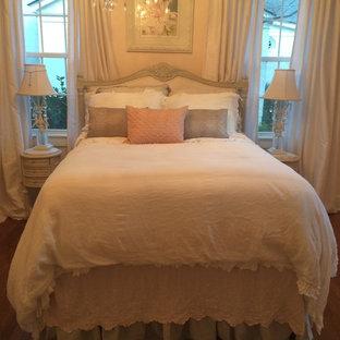 Imagen de habitación de invitados rural, de tamaño medio, sin chimenea, con paredes rosas y suelo de madera oscura