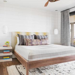 Inredning av ett maritimt sovrum, med vita väggar, mellanmörkt trägolv och brunt golv
