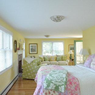 Diseño de dormitorio principal, costero, de tamaño medio, con paredes amarillas, suelo de madera en tonos medios, chimenea tradicional y marco de chimenea de ladrillo