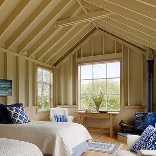 Esempio di una piccola camera degli ospiti stile marino con pareti beige, parquet chiaro e camino ad angolo