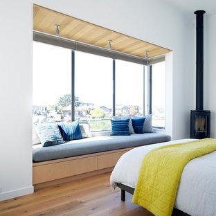 Exempel på ett modernt sovrum, med vita väggar, mellanmörkt trägolv och en öppen vedspis
