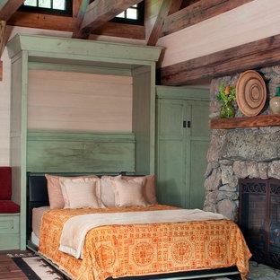 Ejemplo de habitación de invitados rural, pequeña, con suelo de madera en tonos medios, chimenea tradicional y marco de chimenea de piedra