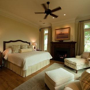 Idée de décoration pour une grand chambre d'amis tradition avec un mur beige, un sol en bois brun, une cheminée standard et un manteau de cheminée en bois.
