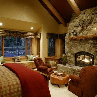 Diseño de dormitorio rural con paredes amarillas, moqueta, chimenea tradicional y marco de chimenea de piedra